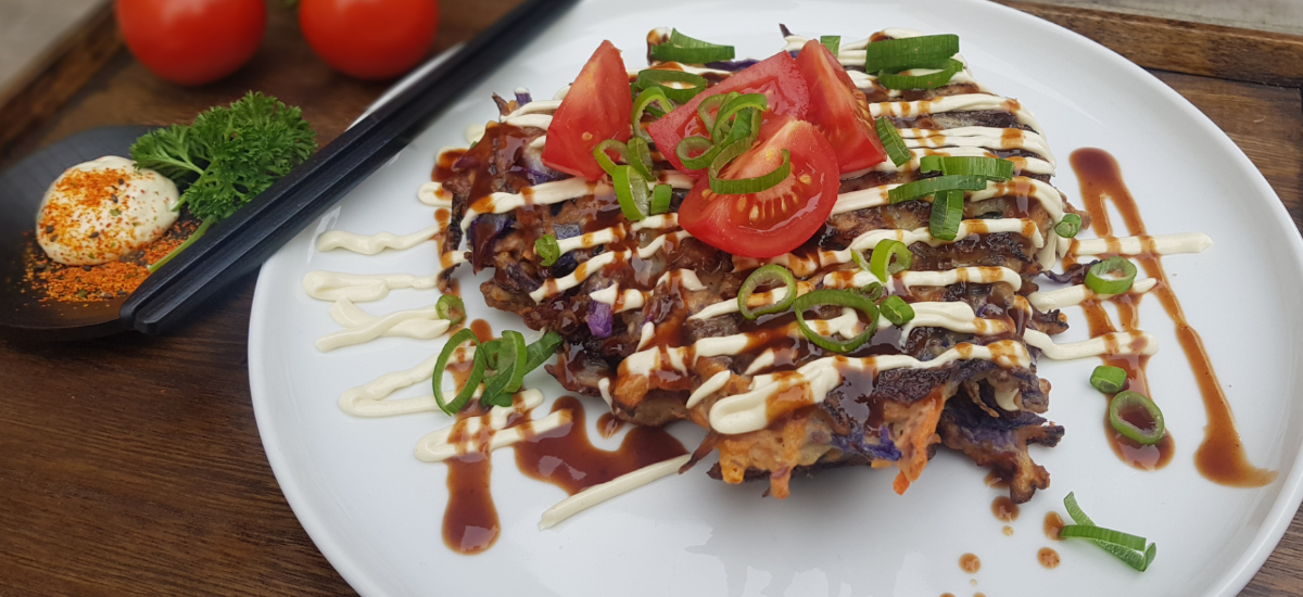 Japanese pancake with okonomiyaki sauce, mayo and tomato salad with sesame dressing