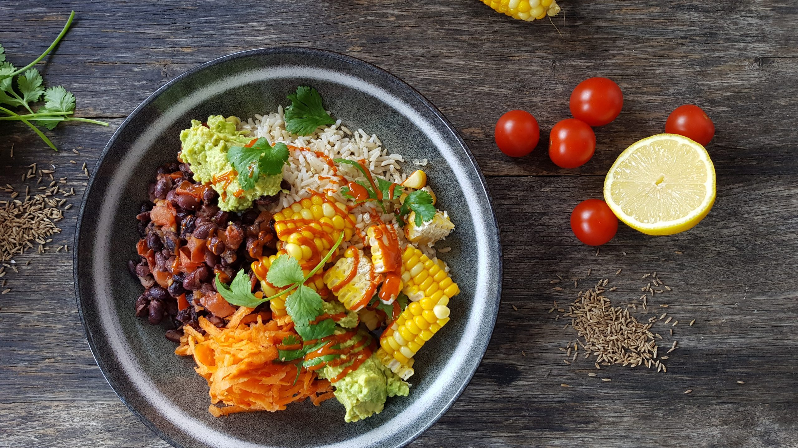 Roast corn burrito bowl with smashed avocado, spicy kidney beans and brown rice